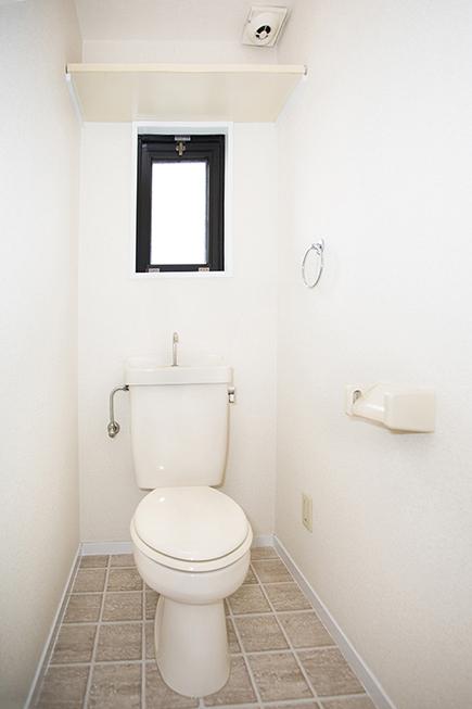 換気扇、棚、タオルかけ、コンセントがついたトイレです。
