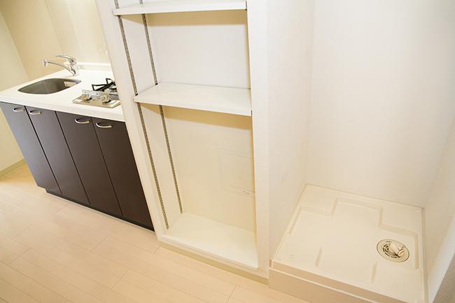 キッチン横並びに、洗濯機スペースとタオルなどを置く棚があります。