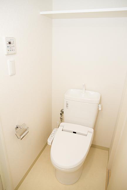 上部に棚のついた、きれいな清潔感のあるトイレです。