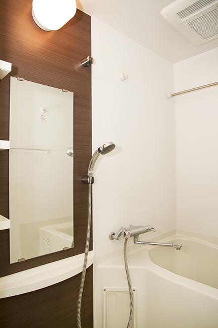 バスルームは、木目の壁に大きな鏡がついています。