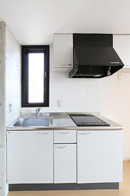フード付きの換気扇とIHがついているコンパクトなキッチン。