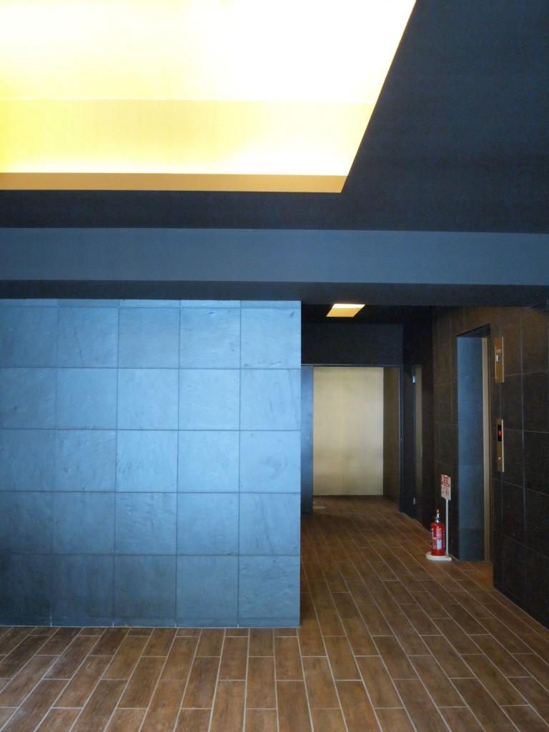 シックなダークグレーの壁に木目調の床のエレベーターホール。