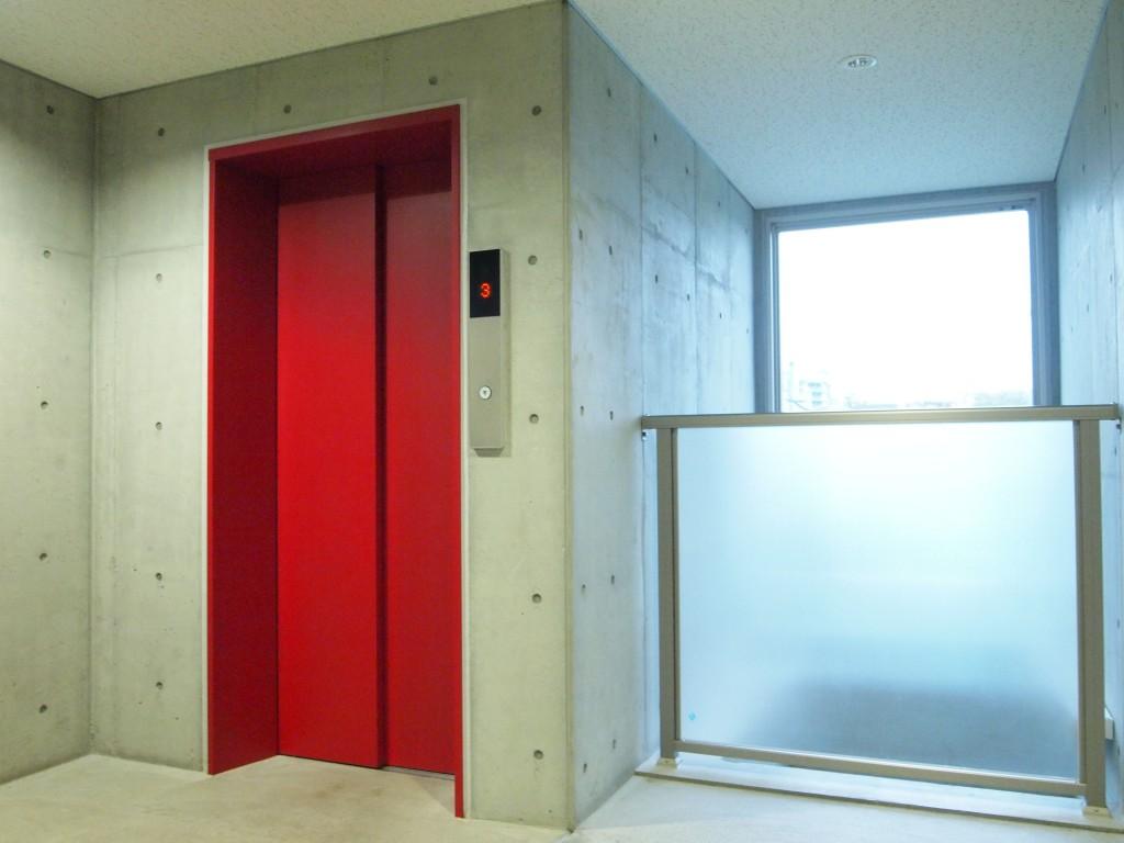 コンクリート打ちっぱなしの建物に、赤いエレベーターが印象的です。