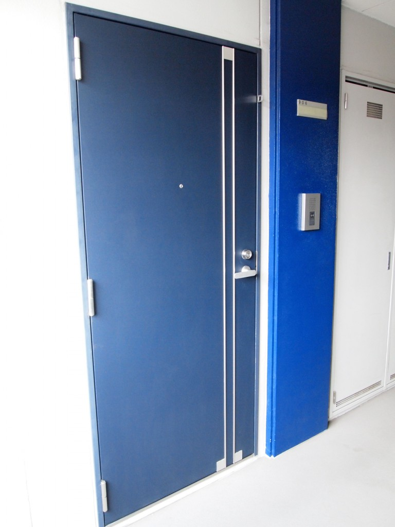 目が覚めるような鮮やかなブルーのドア。906号室