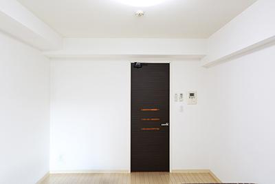 白を基調している壁とマッチする、木目の茶色いドアです。