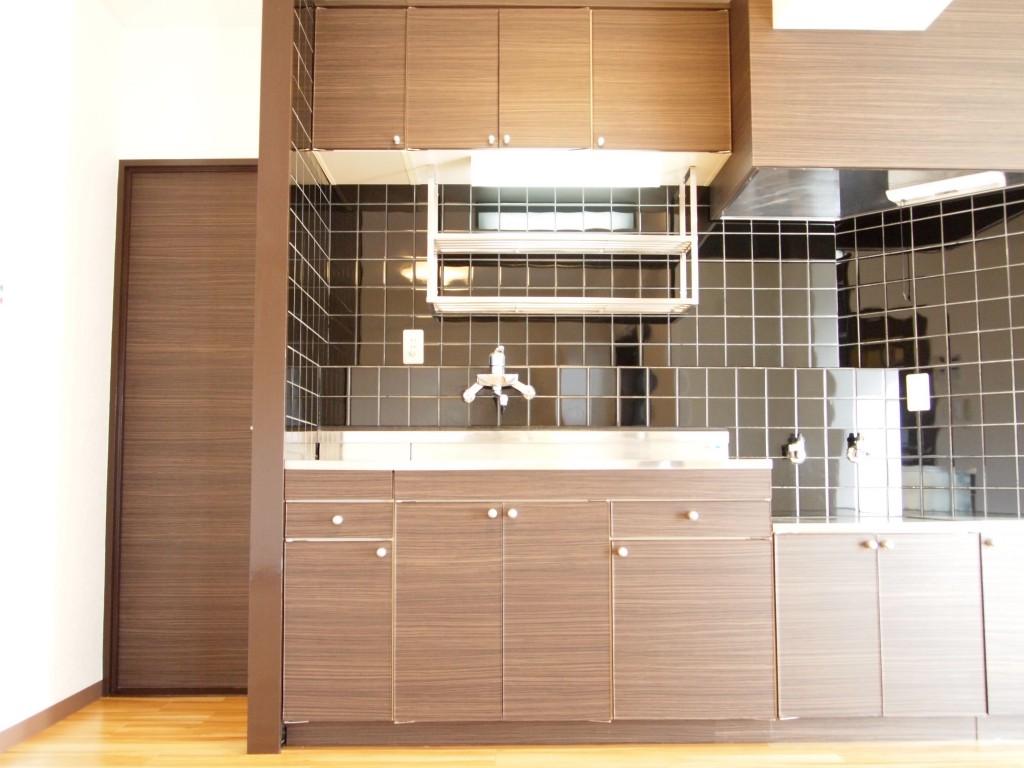 ダークブラウンのシックなパネルと黒のタイルがお洒落なキッチン。