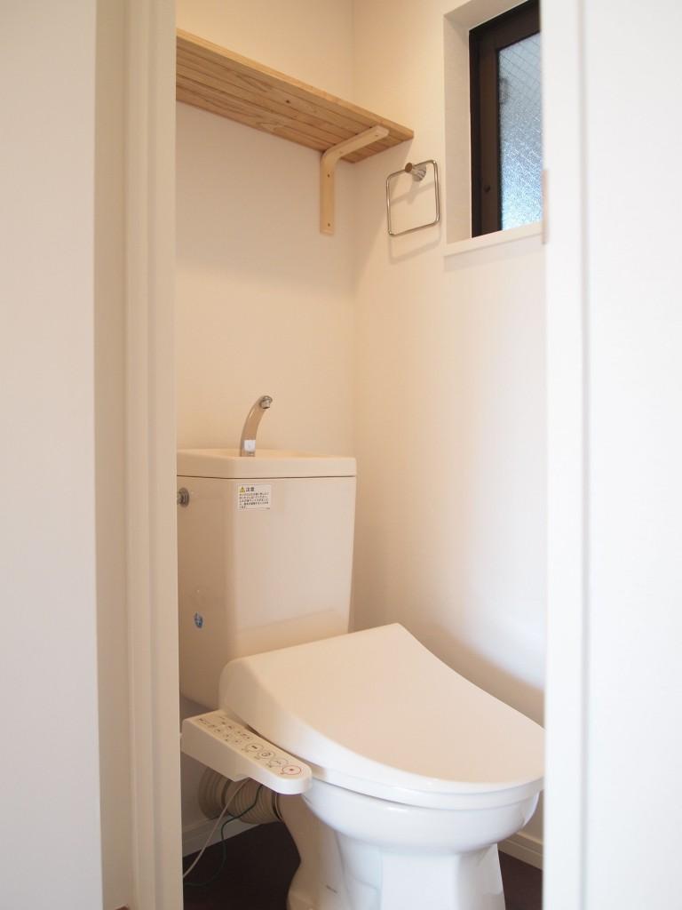 清潔感のあるトイレ。上部には棚もついています。