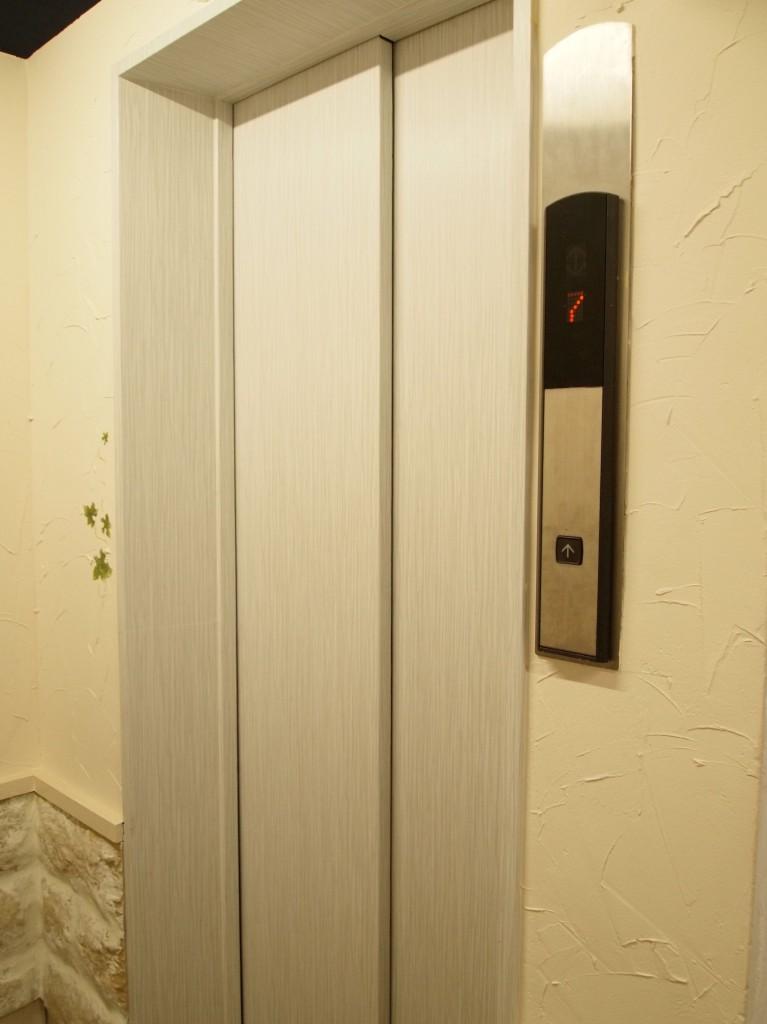 淡い水色のエレベーターの扉。