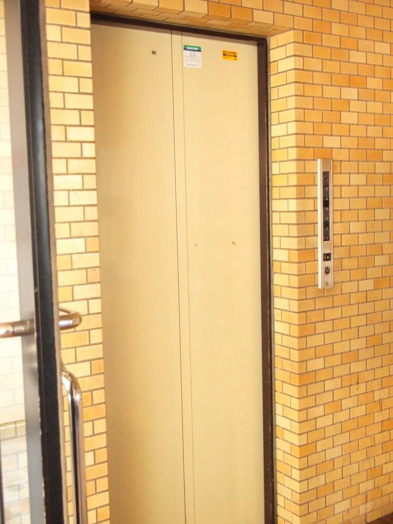 明るい色のレンガ模様に囲まれたエレベーターです。