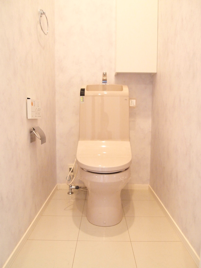 花柄クロスの壁の、清潔感溢れるトイレです。