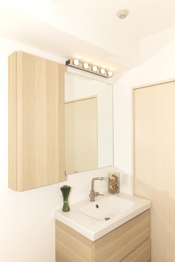 木のぬくもりを感じるシンプルな洗面台は照明もおしゃれ。