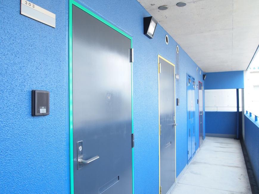 鮮やかな青色の壁に、手前からそれぞれのテーマカラーとなる緑、黄色、赤のドア。