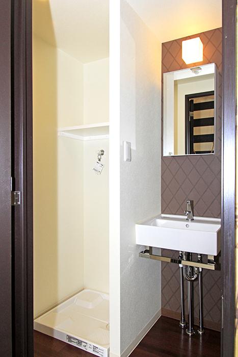 右の扉を開けてみると、清潔感あふれるキレイな洗面と洗濯機置き場があります。