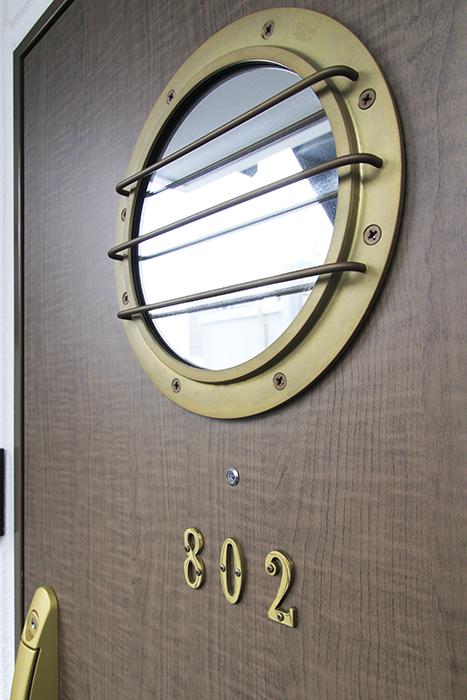 玄関ドアには鏡になった海賊船っぽい窓がついています。