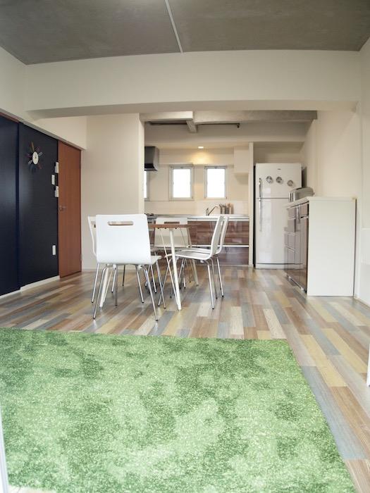 パステルカラーの木目調の床と芝のようなラグが印象的な共有LDK