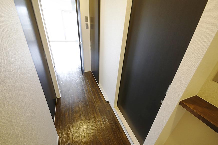 廊下には三つの扉。  左手のドアが5.8帖の洋室、右手の2つのドアが水回り_MG_5090