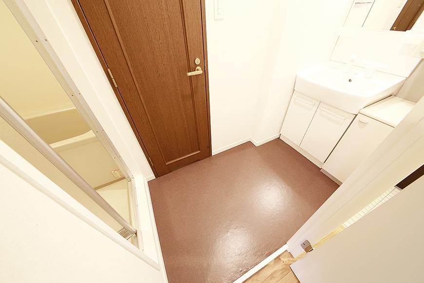 温もりのある内装で落ち着く空間に。右手から独立洗面台、真ん中のドアがトイレ、左手がバスルームとなっております。_MG_9393