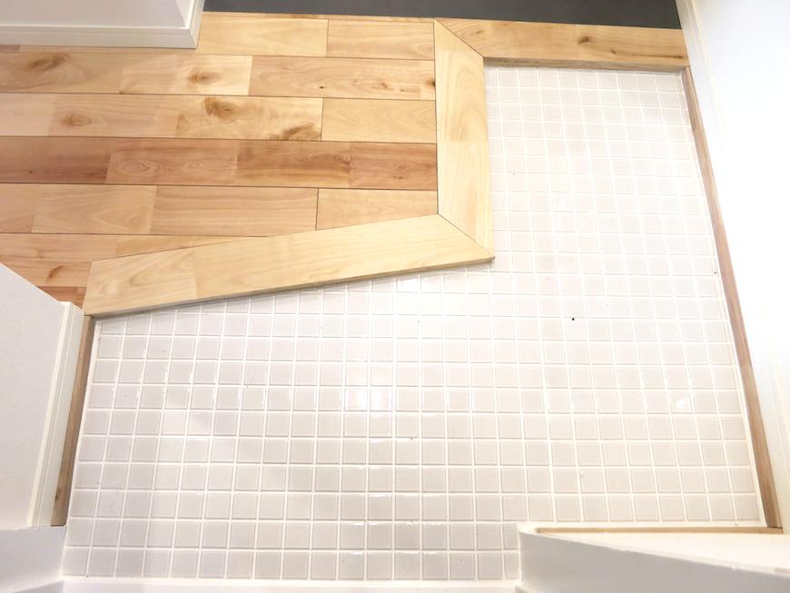 玄関 白いタイルと無垢の床。シンプルでお洒落なTOMOSの玄関 東海御園ハイツ 2