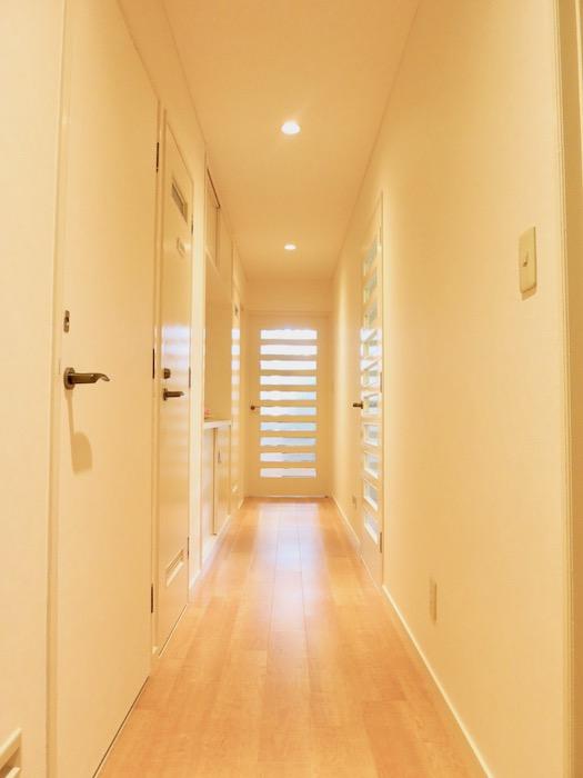 THe PLace  玄関へ向かう廊下。メイプルの床とアイボリーの建具と白いクロスで上品な廊下に。