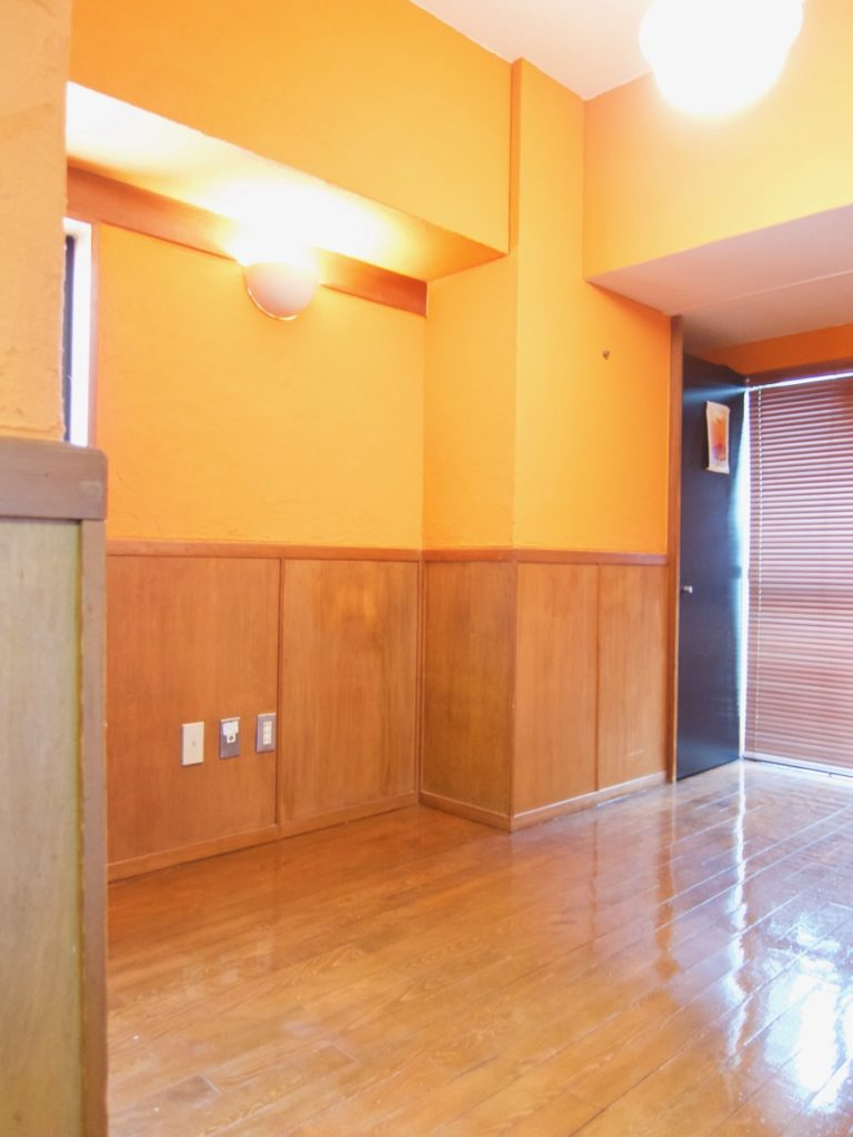 6帖の洋室。オレンジ色の漆喰の壁と味わいある腰壁。ARK HOUSE 8C1