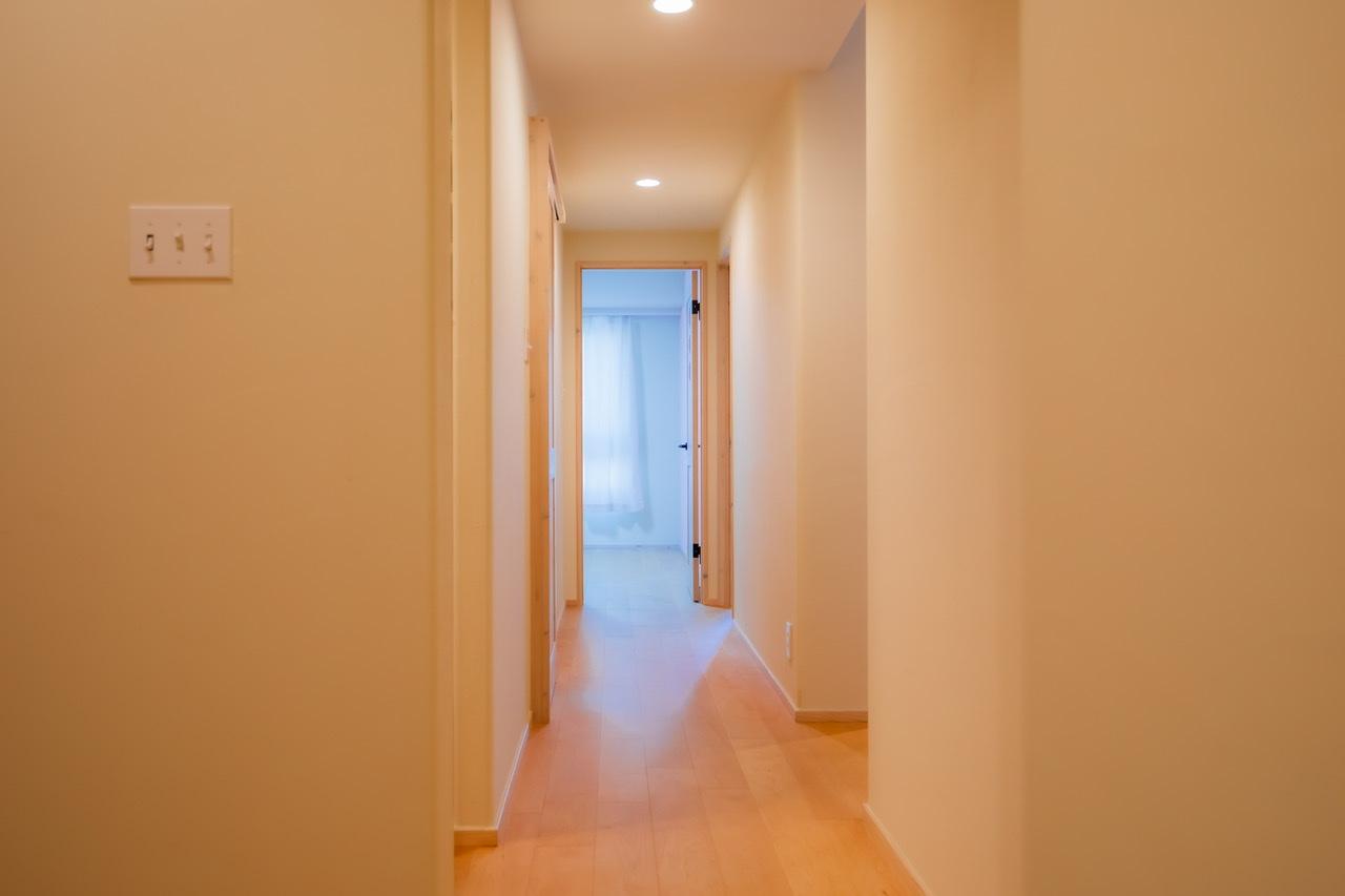 明る光が差し込む洋室が見える廊下